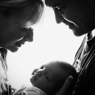 Newborn baby photography photo shoot. Photo with new parents in black and white... Photographer of photo shoot is Cheryl Catton , Woking.