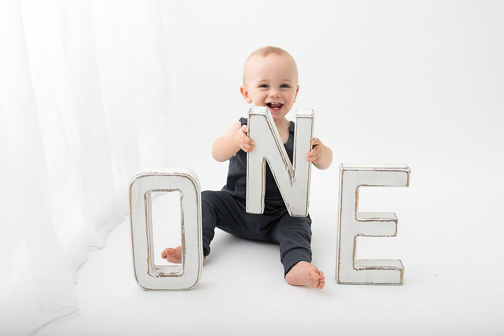 Milestone photography. First birthday photoshoot in Woking. Photographer Cheryl Catton. With letters spelling ONE Woking baby photographer, Woking photographer, Woking newbord photographer, Woking baby photographer