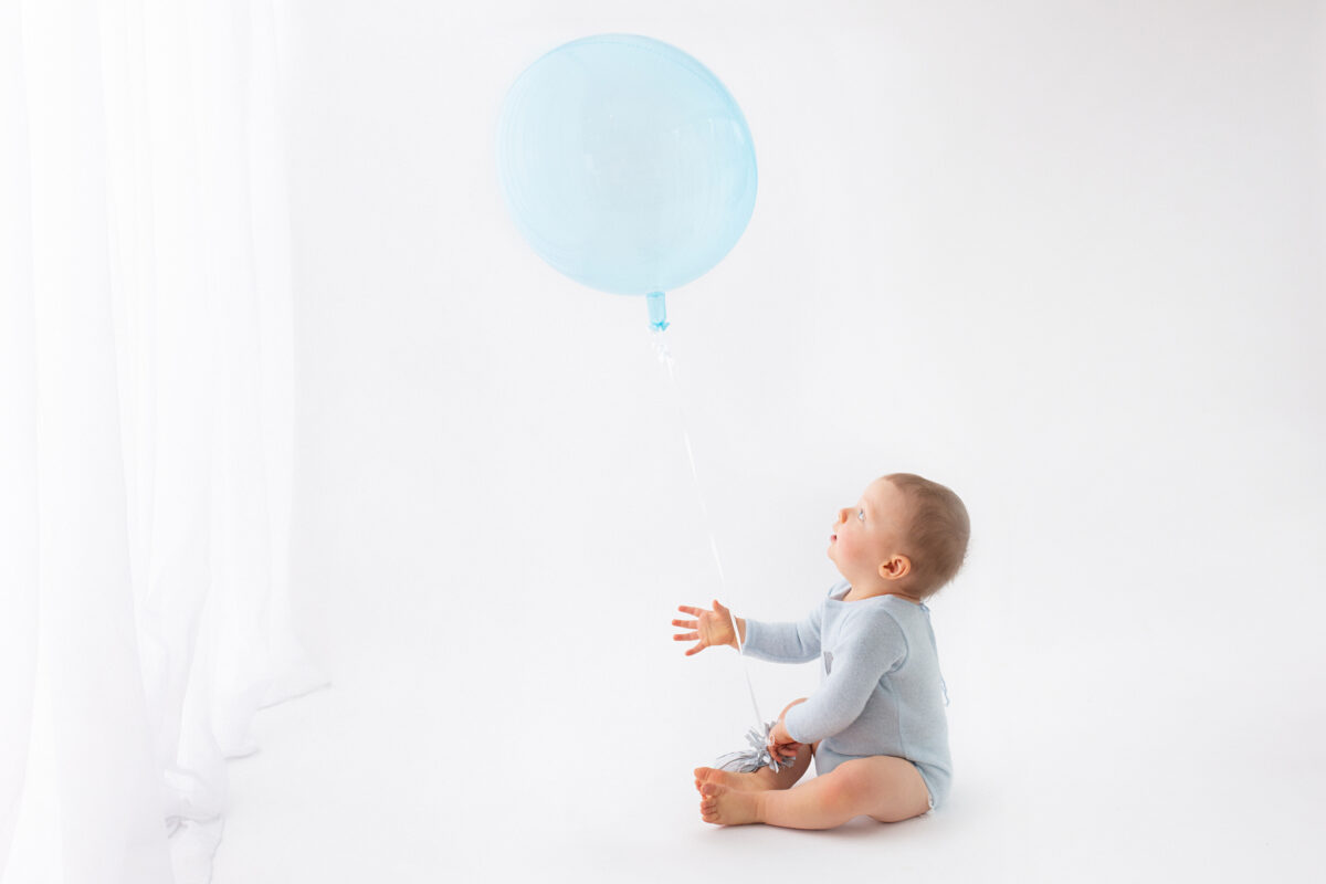 Cakesmash photo shoot, Baby boy playing with balloon during photoshoot, Milestone photography. First birthday photoshoot in Woking, Guildford photographer, Guildford Cake smash photographer, Guildford baby photographer