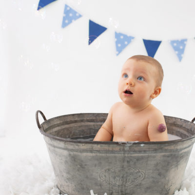 Cakesmash photo shoot. Baby boy in bubble bath for cake smash photoshoot. Milestone photography. First birthday photoshoot in Woking, Guildford photographer, Guildford Cake smash photographer, Guildford baby photographer