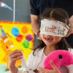 Little girl getting blindfolded for pin the tail on the donkey