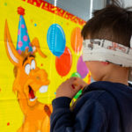 Little boy playing pin the tail on the donkey